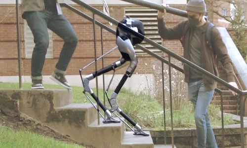 Photo of a bipedal robot going down a set of stairs.